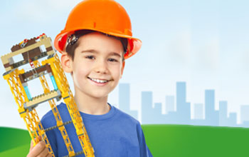 Kid wearing orange construction helmet holding a Lego tower