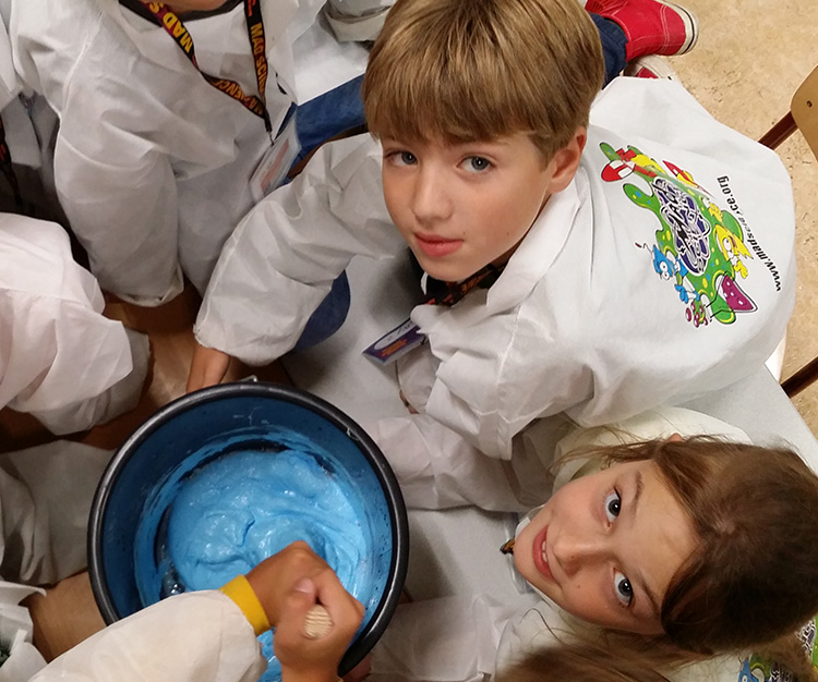 Kids looking up while mixing a big bucket of blue slime